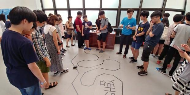 사이언스 바캉스 현장에선 한국공학한림원 산하 학생모임 예스(YEHS)가 주최한 이공계 진로탐구 프로그램도 열렸다. 참가 학생들이 소형 로봇이 줄을 따라 움직이는 '라인 봇' 시연을 살펴보고 있다. - 현수랑 기자 제공